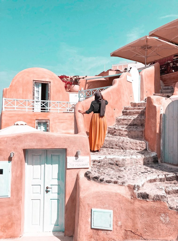 Posing in front of the pink houses in Oia Santorini