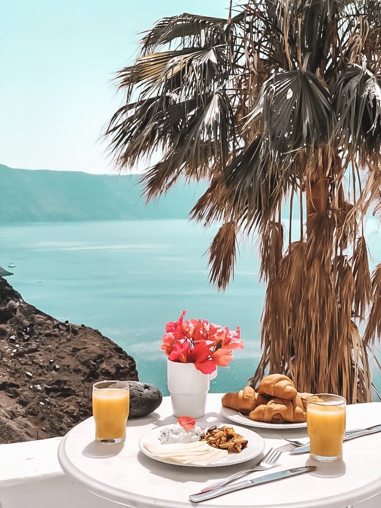 Having breakfast in Santorini with palms on the background.