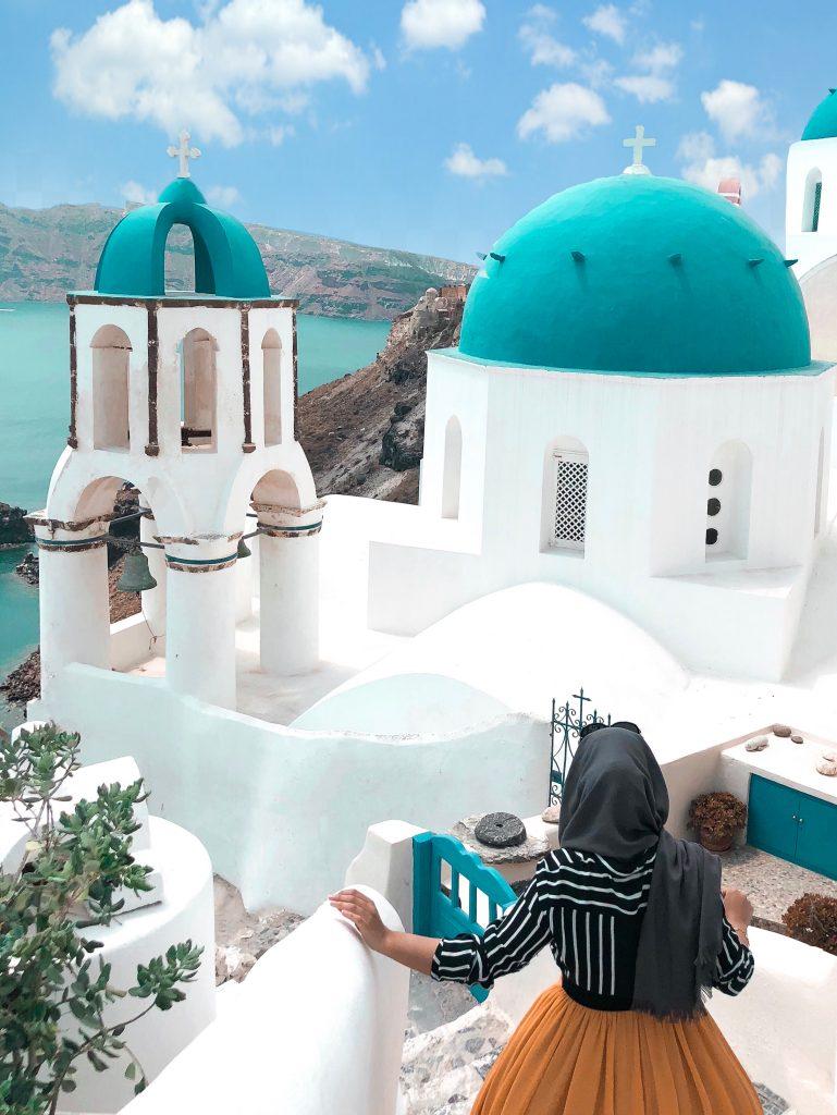 Santorini girl posing near the blue domes